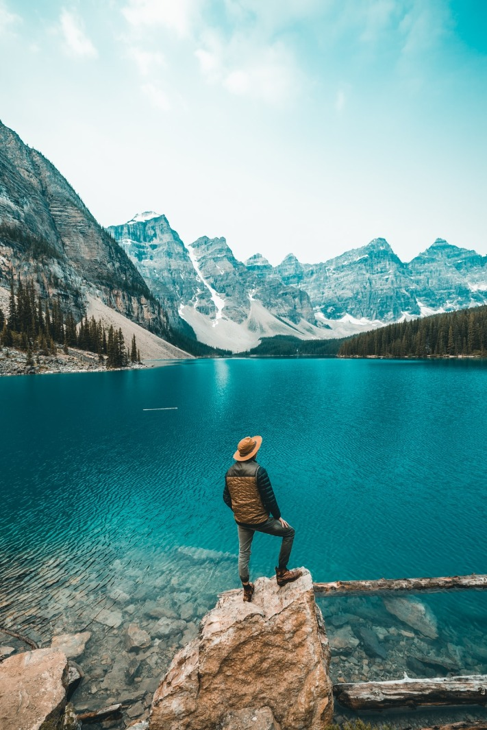 man_standing_on_rock_near_lake