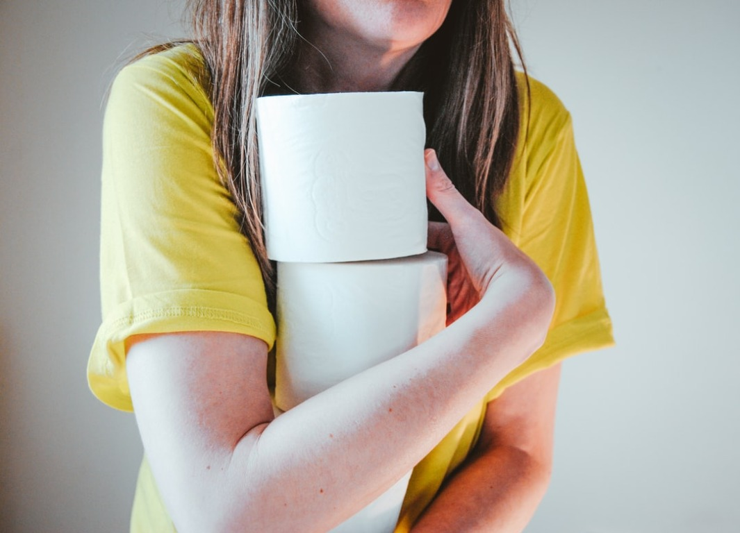 woman_in_yellow_t-shirt_holding_white_tissue_paper
